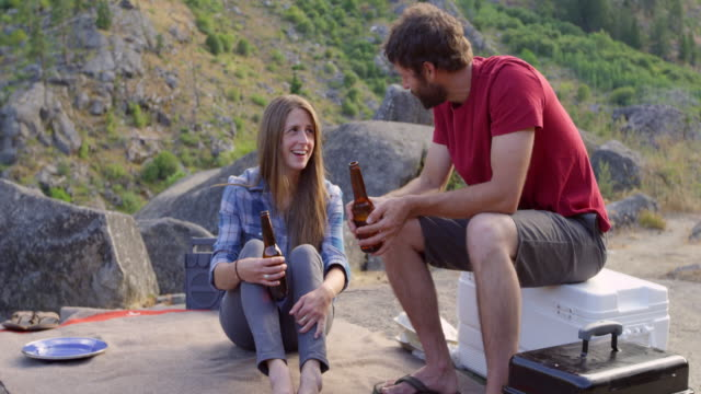 MS Laughing couple talking and drinking beer at campsite