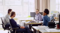 MS laughing coworkers having informal project meeting next to workstations in architects office