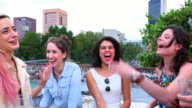 MS PAN Laughing female friends toasting glasses together on rooftop deck