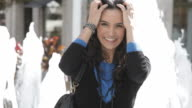 Laughing Hispanic woman standing near fountain