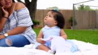 MS Laughing infant girl sitting on blanket with mother in backyard