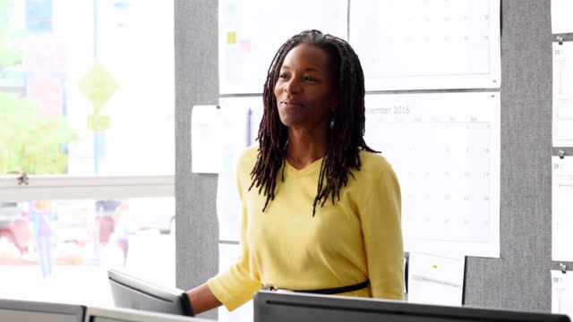 MS Laughing mature businesswoman standing at workstation in office