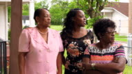 MS Laughing mother and adult daughters standing on front porch of home before church
