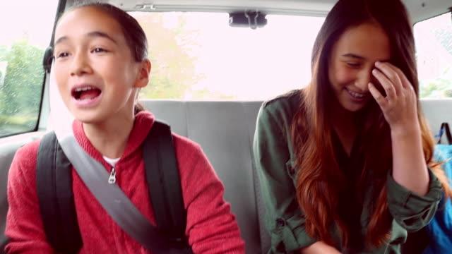 MS Laughing sisters in backseat of van on way to school