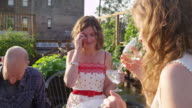 MS Laughing woman sitting drinking wine with friends in rooftop garden on summer evening