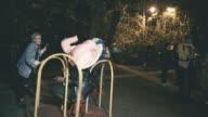 Laughing women pushing man in plush elephant head sitting on roundabout