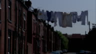 Laundry hangs from a line suspended from terraced houses over a street. Available in HD.