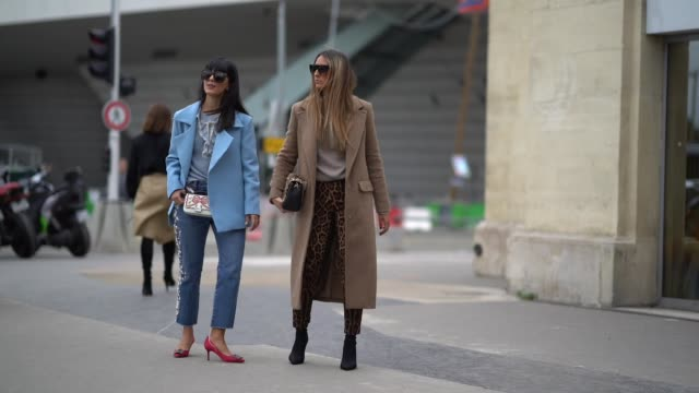 Laura Comolli wears sunglasses a blue jacket a silk top a bag cropped jeans red shoes Elisa Taviti wears sunglasses a beige coat a gray top leopard...