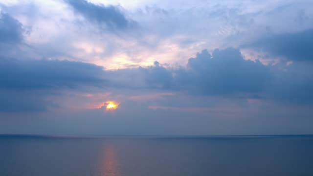 Lavender clouds blanket a glowing pink sun over the calm waters of the Gulf of Mexico.