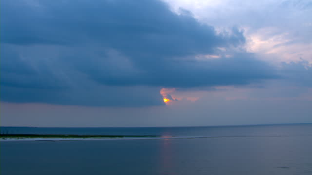 Lavender clouds encroach on a glowing pink sun over the calm waters of the Gulf of Mexico.