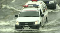 Law enforcement vehicles splash water as they drive a flooded street in Thailand