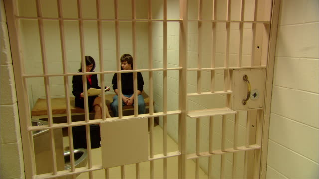 MS Lawyer arriving and being let into cell with teenage prisoner/ Lawyer and teenage boy sitting down to look at documents/ New Jersey