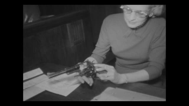 Lawyers defendants talking in hallway woman examining a revolver submitted as evidence