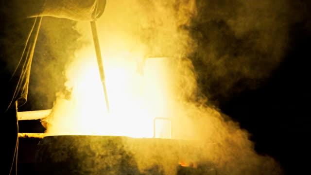 Geschichtete weißer Rauch und Feuer aus Hochöfen. Verarbeitung von Stahl in Eisengießerei Pflanze.