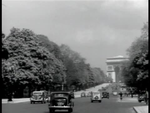 PARIS FRANCE CU 'Le Grande Hotel Paris' travel sticker LS ChampsElysees w/ traffic WS Arc de Triomphe BEHIND Painter in Palais des Tuileries garden...