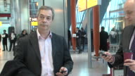 UKIP leader Nigel Farage waits in Heathrow Airport after arriving on a flight from Washington DC Tieless he chats to aide talks on mobile phone and...