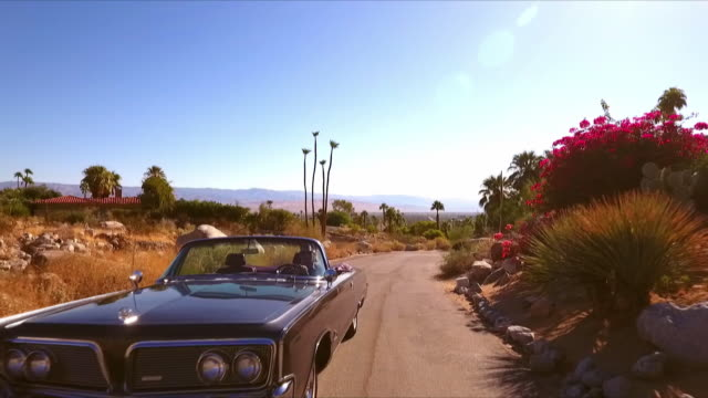 TS CS leading classic convertible automobile driving uphill on deserted road in California desert town