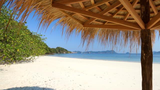 Blatt Sonnenschirm am tropischen Strand mit weißem Sand.