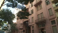 Leafy trees frame an apartment building in Porto Alegre, Brazil.