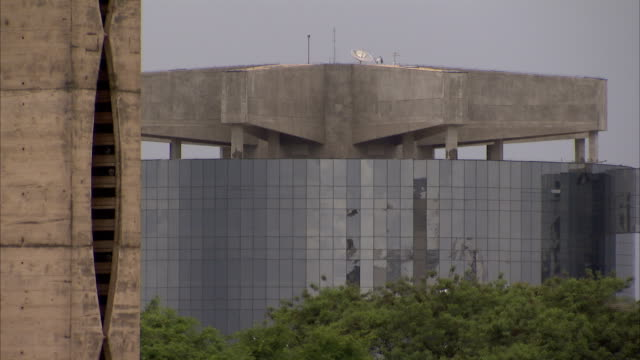 Leafy treetops frame a modern building in Brasilia. Available in HD.