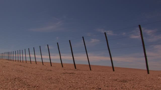 A leaning fence divides property in the Namib Desert of Namibia. Available in HD.