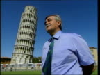 Leaning Tower of Pisa saved from collapse CMS Woman tourist holding bars of barrier Male tourist taking photograph CMS Male tourist looking thru...