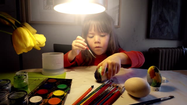 Processo di apprendimento-piccola bambina dipinto Uova di Pasqua a casa