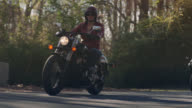 SLO MO. Leaves blow on forest road as three women cruise by on motorcycles.