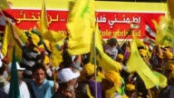 Lebanese supporters of Hezbollah chanting at rally waving Hezbollah and Syrian flags many wear yellow caps