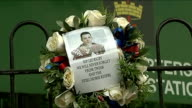 Woolwich attack first anniversary London Woolwich EXT Wreath with picture of Lee Rigby on fence outside army barracks