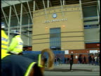 Leeds Elland Road GV Entrance to 'Leeds United AFC' as policemen on horses along Leeds fans towards MS Sign on wall of football stadium 'Leeds United...