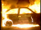 Leeds Harehills GVs Burning car in street NIGHT GV Police in riot gear marching along past burning mattresses BVs Riot police facing stone throwing...