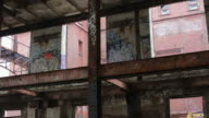 Left to right pan of the graffitti covered walls of an abandoned building