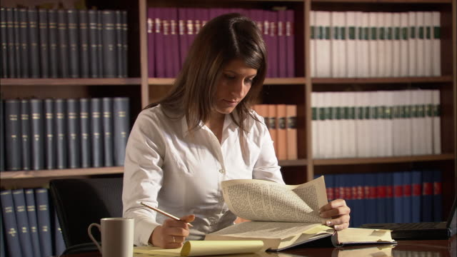Legal intern flipping through legal documents and taking notes in law library / Rome, Italy