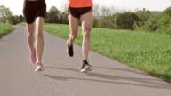 SLO MO TS Legs of a couple running on asphalt