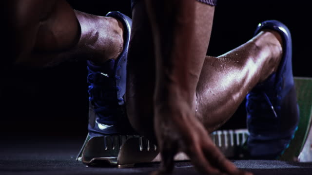 SLO MO Legs of a male African-American sprinter starting from the starting block