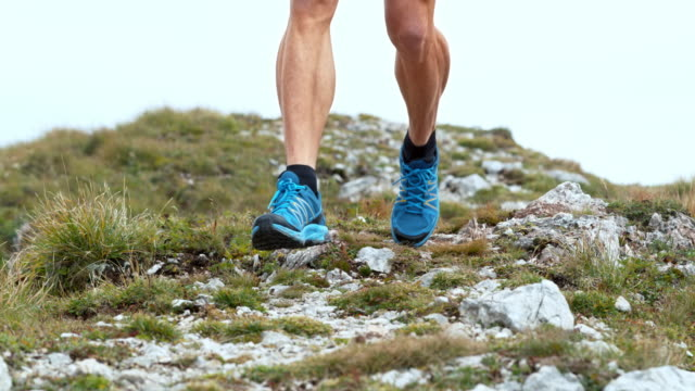 SLO MO Legs of a male runner running down the mountain on a rocky trail
