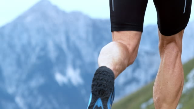 SLO MO Legs of a male runner running high in the mountains