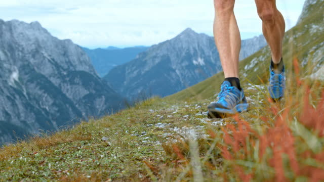 SLO MO Legs of a male runner running on a meadow high in the mountains
