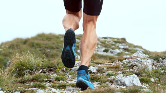 SLO MO Legs of a male runner running up the mountain on a rocky trail