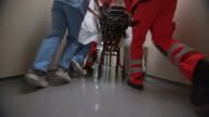 DS Legs of a medical team bringing a patient on the stretcher into the ER