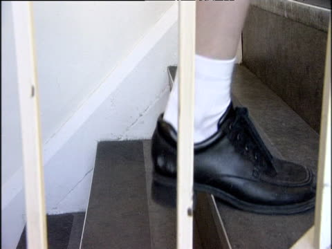 Legs of anonymous secondary schoolgirls walking and running up stairwell East Barnet School North London