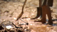 Legs of barefoot male in long shorts standing in wet red clay mud next to legs in muddy rubber boots shovel shoveling pushing mud from neighborhood...