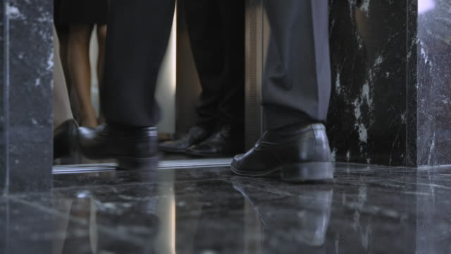 LD Legs of business people as they are entering the elevator