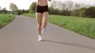 SLO MO TS Legs of female marathon runner on asphalt