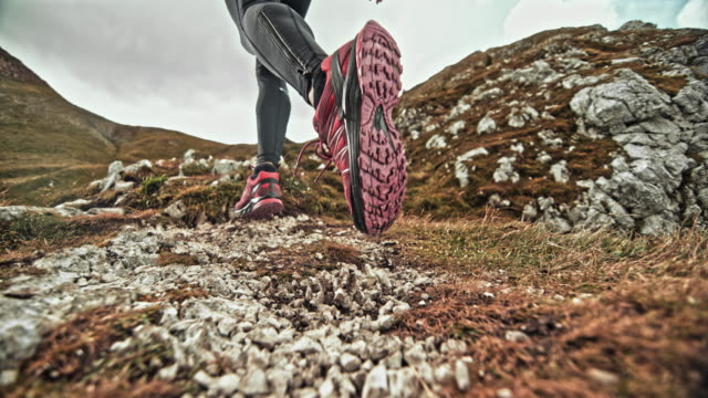 SPEED RAMP Legs of female runner running on a mountain trail scattering gravel