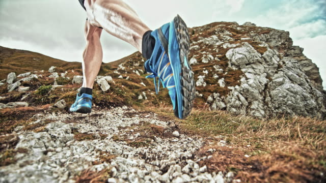 SPEED RAMP Legs of male runner causing gravel to scatter on a mountain trail