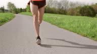 SLO MO TS Legs of male runner moving on asphalt