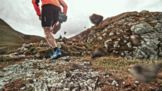 SPEED RAMP Legs of male runner running on a mountain trail scattering gravel into the camera
