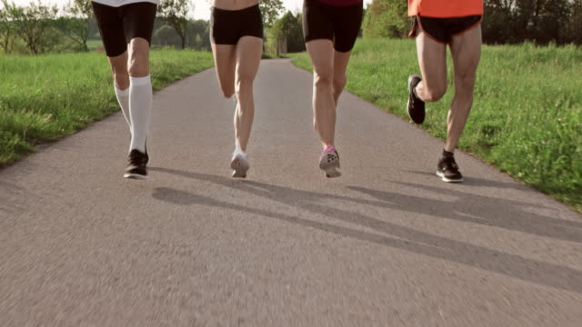 SLO MO TS Legs of runners running on a road